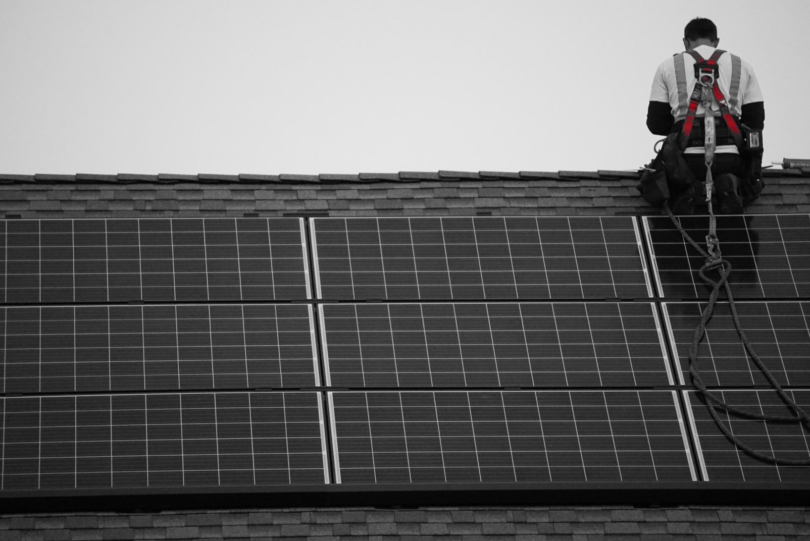 Black and white photo of man doing solar panel removal and reinstallation in black and white