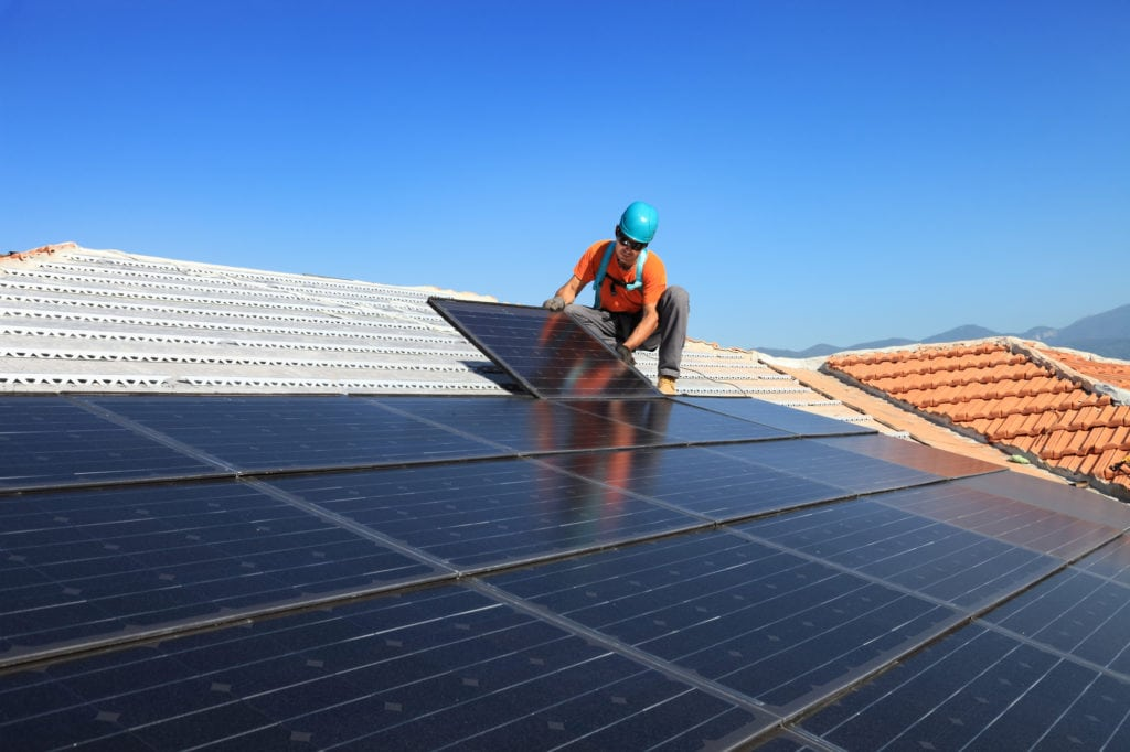 man installing solar panels on a roof for reinstallation