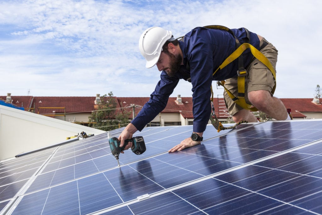 man drilling solar panels down wearing a hard hard during a solar reinstallation and replacement job.